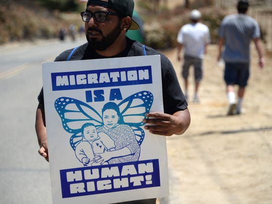 A counter-protestor holds a sign supporting immigration outside a U.S. Border Patrol facility in Murrieta during an anti-immigration protest in Murrieta, California.