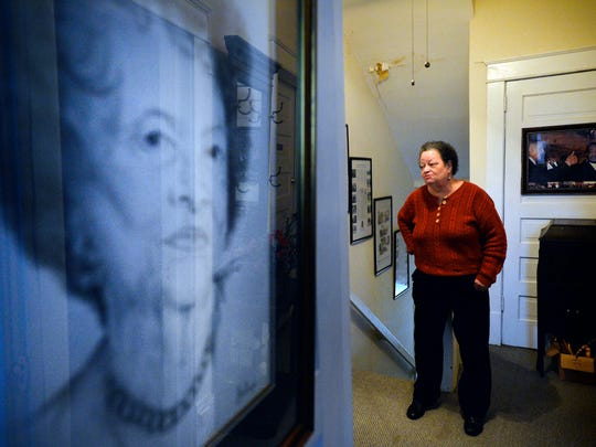 Ruth Ann Butler, director of the Greenville Cultural Exchange Center, stands near a charcoal drawing of Alberta Tucker Grimes.