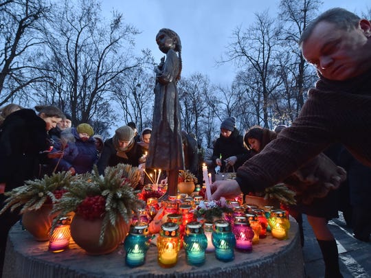People place candles in memory of the victims of the Holodomor famine during a ceremony at the Holodomor memorial in Kiev on November 22, 2014. Ukraine marked 81 years since the Stalin-era Holodomor famine, one of the darkest pages in its entire history that left millions dead and which is regarded by many as a genocide. The 1932-33 famine took place as harvests dwindled and Soviet leader Josef Stalin's police enforced the brutal policy of collectivising agriculture by requisitioning grain and other foodstuffs.