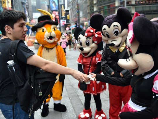 A tourist tips a Minnie Mouse character after posing for a photograph with the cartoon figures this week in New York's Times Square. The panhandler characters pose for tourists and work for tips, which sometimes leads to disputes.