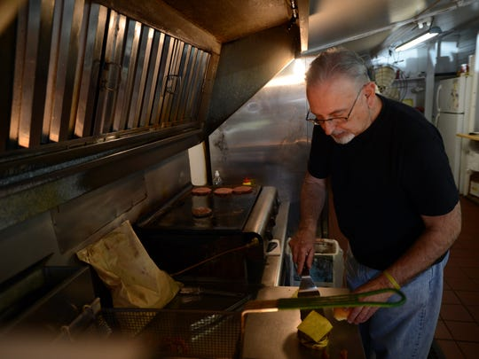Keith Allen works the grill by filling a double cheeseburger order during the lunch rush at Wolff's Sandwich Shoppe on Tuesday, april 22, 2014. Restaurant owner Ron Wolff recently celebrated 30 years of business at his Atlantic, Va. location.