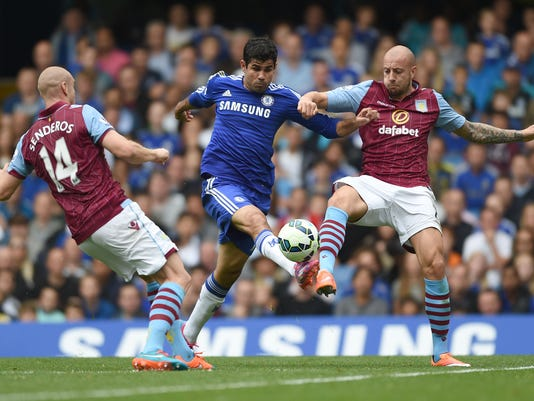 Chelsea's Diego Costa, centre, competes for the ball with Aston Villa players Philippe Senderos, left, and Alan Hutton during their English Premier League soccer match at Stamford Bridge, London, Saturday, Sept. 27, 2014. (AP Photo/Tim Ireland)