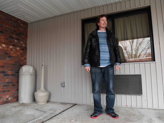 Adam Richey smokes outside his room at the Relax Inn in Laurel on Wednesday.