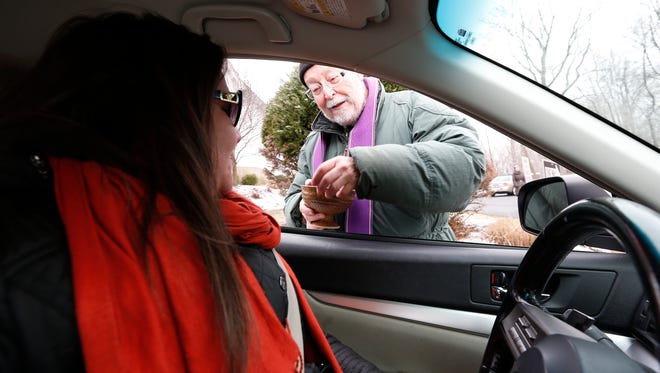 Santina Vitale of West Nyack receives ashes in her car from Reverand Dan Ramm interim pastor at the Clarkstown Reformed Church in West Nyack on Wednesday, Feb. 10, 2016.