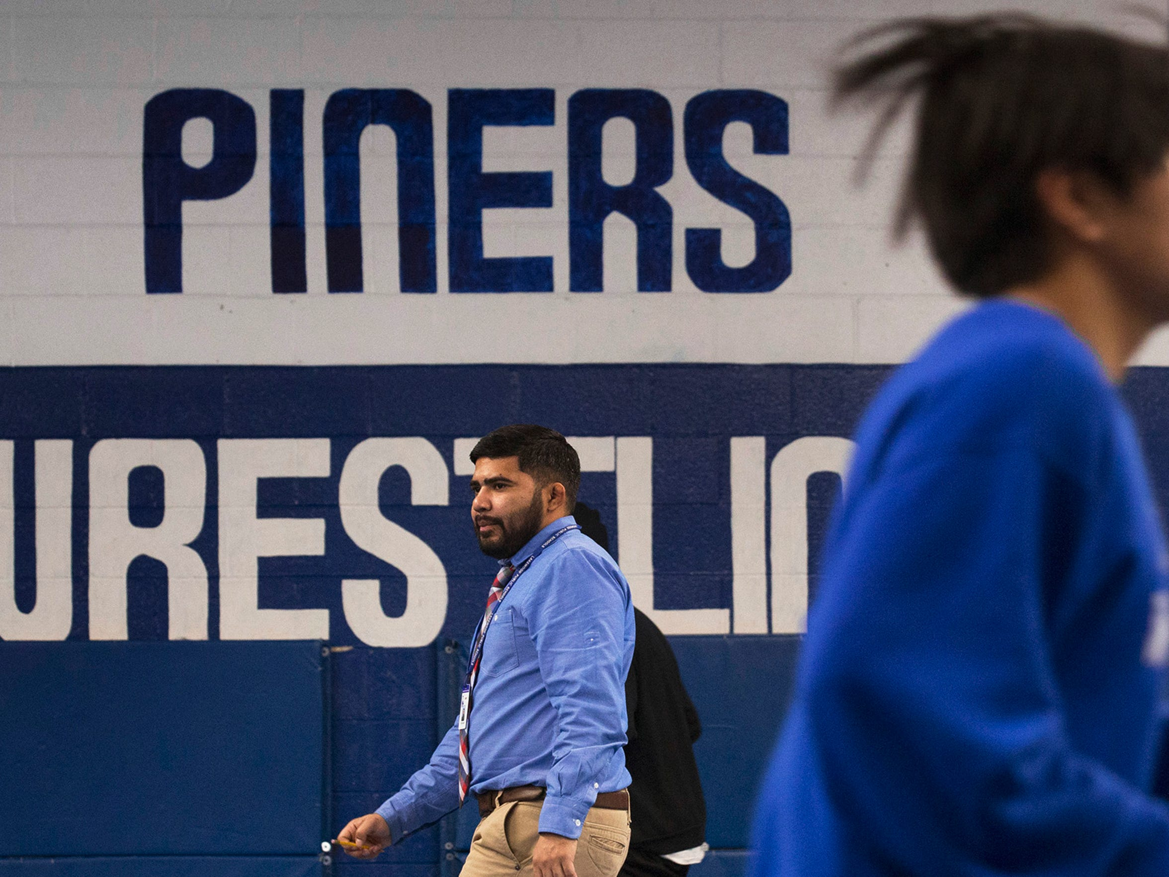 Lakewood High School Wrestling Coach Oscar Orellana with his team as they warm up before a match against Camden and during the match.