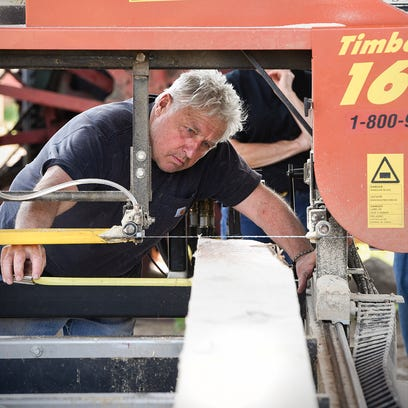 Members of the Central Minnesota Blacksmiths club saw pine trees into dimensional lumber Thursday, May 19, to build a new blacksmith shop at the Albany Pioneer Days grounds. Club members have harvested and cut the lumber and will forge all the nails and hardware for the building by hand.