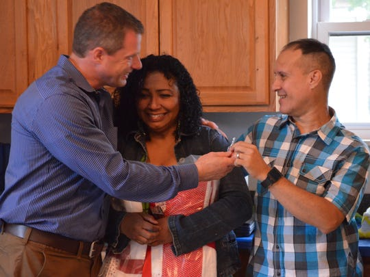 Robert Scarpa, executive director of Cumberland County Habitat for Humanity, presents Maritza and Eliezer Duprey with the key to their new Habitat for Humanity home in Vineland.