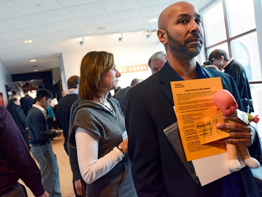 "In this file photo, Michael Black stands in line holding his ""baby"" while taking part in the Community Progress Council hands-on, interactive poverty simulation, Thursday, Jan. 29, 2015."