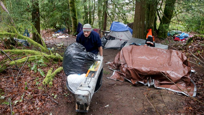 A resident of a homeless camp uses a wheelbarrow to help clean up an encampment before he and other residents were forced by the county to move out in 2018. Pendleton Place, Kitsap's first permanent supportive housing facility, will provide 72 units to homeless people who are suffering from mental illness and substance-abuse issues.
