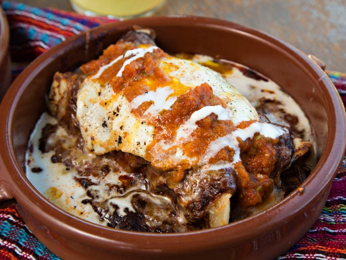 Pork enchiladas topped with an egg, made for us by Aaron Pool of Gadzooks enchiladas and soup, as seen in Phoenix.