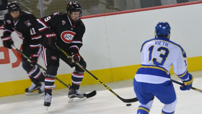 St. Cloud State's Joey Benik (9) controls the puck with Alaska's Austin Veith defending Friday at Sullivan Arena in Anchorage, Alaska. Benik had a goal and Charlie Lindgren had 14 saves for the Huskies in a 3-0 win in the Kendall Hockey Classic.