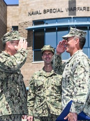 Rear Adm. Tim Szymanski (left) salutes Rear Adm. Brian L. Losey during the Naval Special Warfare Command change of command ceremony at Naval Base Coronado.