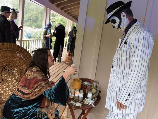 """Megan Morris, left, entices Phillip Quick with a special potion at Treasure Coast Wildlife Center's """"Ghoula"""" fundraiser on Oct.28 in Indiantown."""