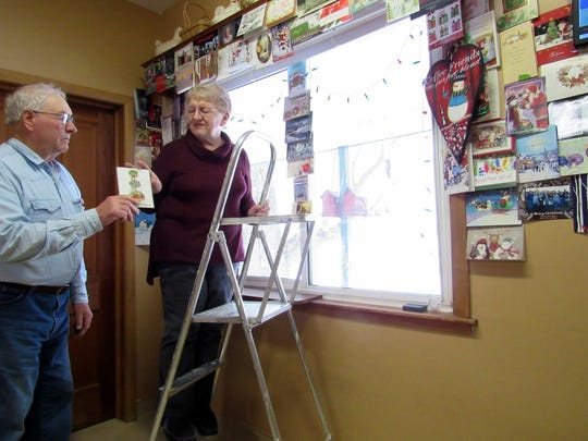 Bob helps Susan hang Christmas cards from family and reader friends.