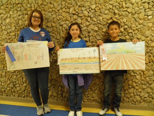 Amanda Warren, left,  fourth grade teacher at Veribest Elementary, displays Xander Colon's first place conservation poster. Cash Vinson, second place winner, is not shown. Other fourth grade winners are; Damaris Rocher, third place and Ruben Rivas, fourth.
