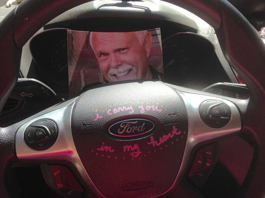 Chuck Dearing's picture rests behind the steering wheel of Alison Miller's pink car. It's one of the ways she remembers her husband.