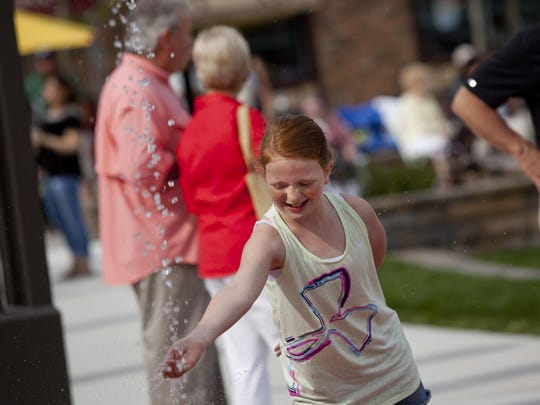 Mara Schweihofer, 10, of Marysville, plays with water from the fountain during the grand opening of the Riverview Plaza courtyard Thursday.