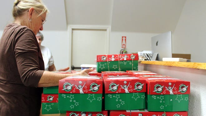 Judy Bryant, wife of the Grace Baptist pastor, organizes shoeboxes before packing them into their shipping case.