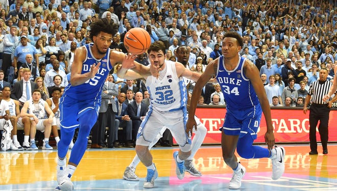 Duke Blue Devils forward Marvin Bagley III (35) and forward Wendell Carter Jr (34) fight for the ball with North Carolina Tar Heels forward Luke Maye (32) in the second half.