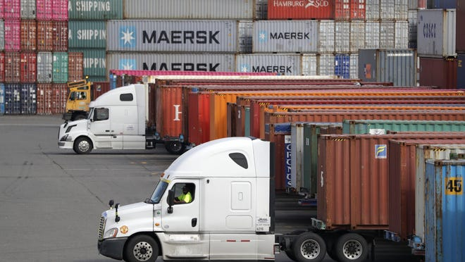FILE - In this Oct. 2, 2019, file photo trucks are positioned to haul shipping containers at a terminal where containers are stacked five-high on Harbor Island in Seattle.