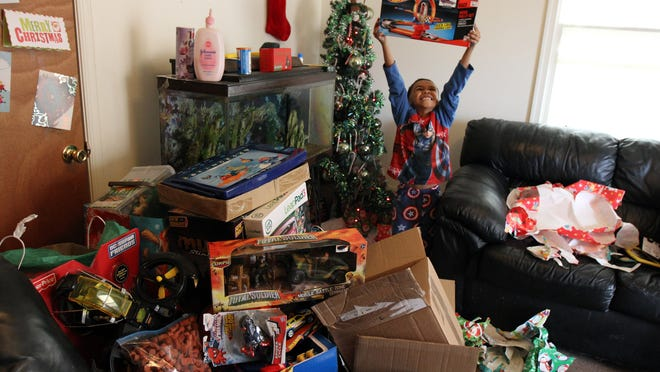 Emmanuel Bellamy, 6, who is being raised by Vatima Bellamy of Asbury Park, a recipient of the Helping Hands, a series in which the Asbury Park Press reached out to readers to help those at the Shore in need, opens donated gifts in their apartment on Christmas Day, Thursday December 25, 2014.
