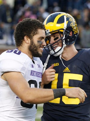 Northwestern's Austin Carr and Michigan quarterback Jake Rudock talk as they get ready to leave the field after Michigan's 38-0 win Saturday.