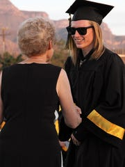 Alamogordo Public Schools Board Member Carol Teweleit hands a 2018 graduate her diploma Friday evening.