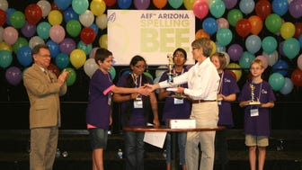Marcus Behling (second from left) accepts his trophy March 21 after winning the Arizona Spelling Bee. Marcus is one of two spellers representing Arizona at this year's national bee.