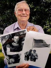 Billy Genaust shows off two of his favorite photos of his great uncle Sgt. William H. Genaust at his home in Effingham, Ill. on Wednesday, June 27, 2007. Avoiding unexploded grenades and hacking their way through cactus under a blazing sun, an American search team has located two caves where they believe a Marine who filmed the iconic flag-raising on Iwo Jima may have been killed 62 years ago in one of World War II's most symbolic battles. (AP Photo/Seth Perlman)