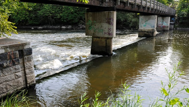 Water flows over the dam on the Sauk River near Whitney park in this photograph taken Aug. 6, 2014. The City of St. Cloud plans to remove the dam.