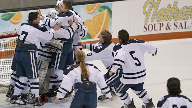 Pittsford players mob starting goalie William Hernes as they celebrate their 4-2 championship game win over Fairport.