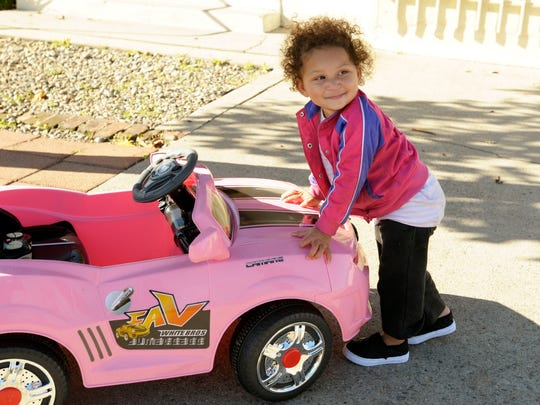 Kimberly Brindle, not pictured, and her daughter, Heaven, 1, play with Heaven's new remote controlled Camaro near their home in Visalia.