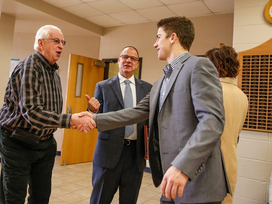 """Dave Green, left, tells Scott Heady's son, Luke, 16, that he's known him since he was just """"a little guy,"""" before Heady is official announced as the head coach of the Marian University Knights' men's basketball team on Monday, Feb. 20, 2017. Green met Scott Heady at Warren Central where they were both involved in athletics."""