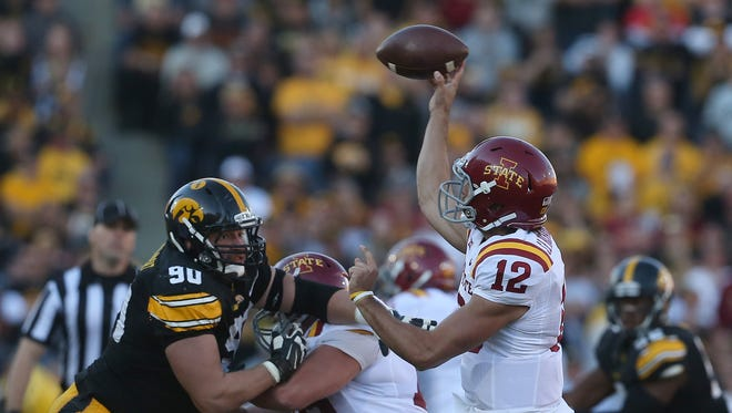 Iowa State quarterback Sam Richardson gets a pass off as Iowa right tackle Louis Trinca-Pasat rushes him on Saturday, Sept. 13, 2014, at Kinnick Stadium in Iowa City, Iowa.