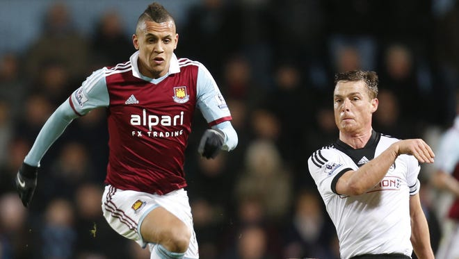 West Ham United's Ravel Morrison, left, controls the ball past Fulham's Scott Parker, during their English Premier League soccer match in London.
