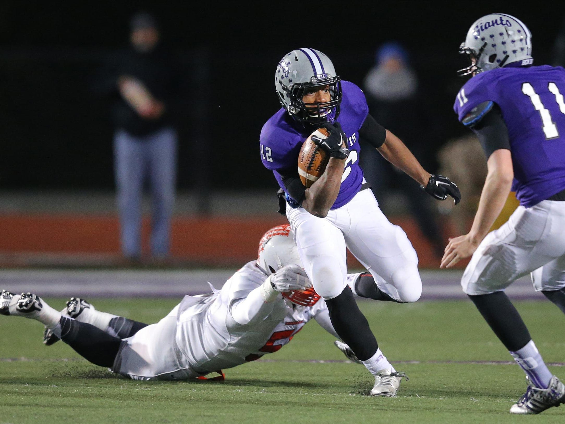 Ben Davis running back Chris Evans breaks a tackle from Center Grove player Jovan Swann on a long touchdown run in the first half of the IHSAA Semi-State game held at Ben Davis High School on Friday, Nov. 14, 2014.