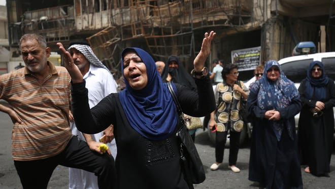 Iraqis  lament the loss of lives at the site of a suicide bombing in a busy Baghdad shopping area July 3, 2016.
