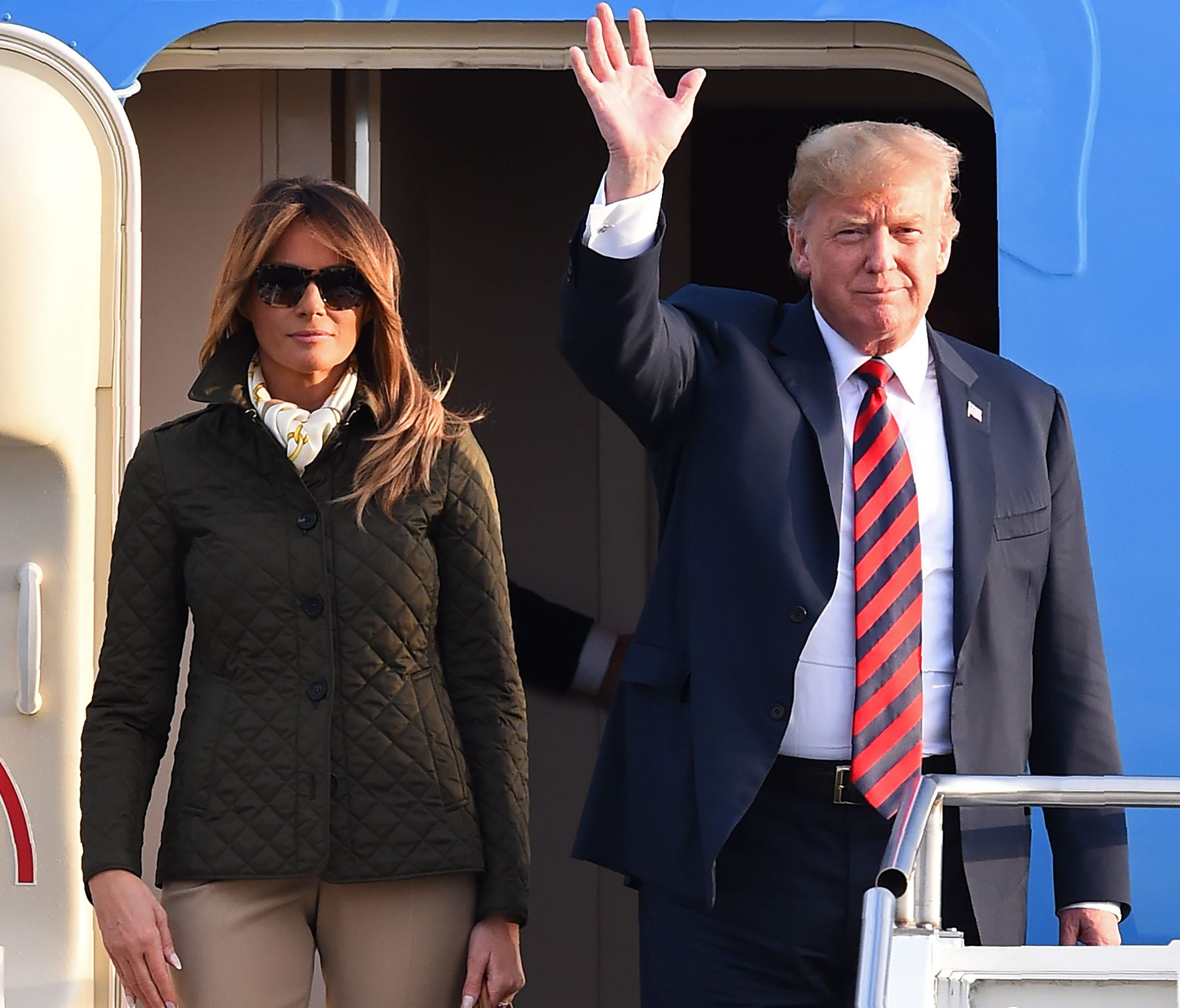 President Donald Trump waves as he disembarks Air Force One with first lady Melania Trump at Prestwick Airport, south of Glasgow.