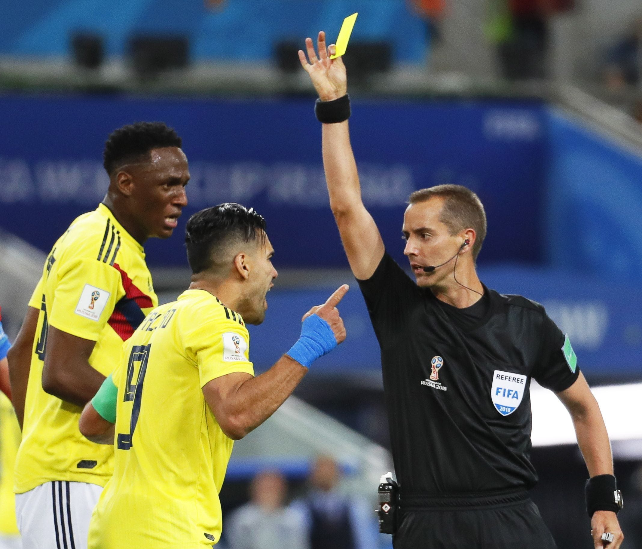 Mark Geiger gives Radamel Falcao (No. 9) of Colombia a yellow card during the World Cup match against England.