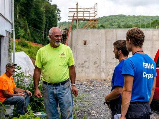 Kevin Schiman and another member of the Blue Eight talk with a man they are working with in White Sulphur Springs, West Virginia.