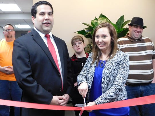 Sandco Industries board president Chris Caputo stands beside CEO Megan Craun as she snips the ribbon at the grand opening of Sandco's new 30,000-square-foot plant in Clyde.