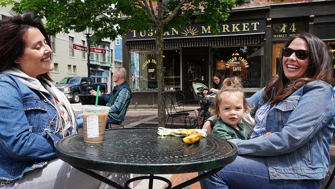 Kayleigh Bullock of Portsmouth, and Lindsey Cougherty with her daughter Poppy Smith 2 1/2, of Nottingham, enjoy some time outdoors at Tuscan Market in Portsmouth on Tuesday.