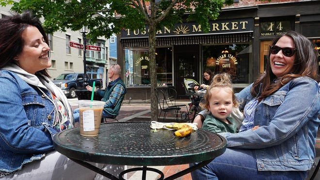 Kayleigh Bullock of Portsmouth, and Lindsey Cougherty with her daughter Poppy Smith 2 1/2, of Nottingham, enjoy some time outdoors at Tuscan Market in Portsmouth Tuesday.