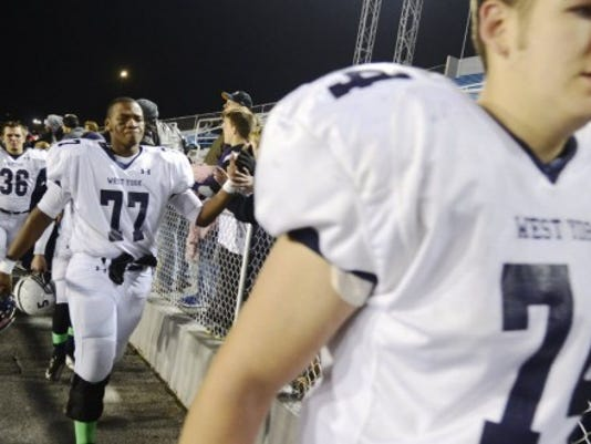 West York players, from left, Alex Raffensberger, Ay'Keil Marshall, and Aaron Sowers high-five fans after losing 21-10 to Bishop McDevitt in the District 3 Class AAA championship game at Hersheypark Stadium on Friday, November 30. DAILY RECORD/SUNDAY NEWS - KATE PENN