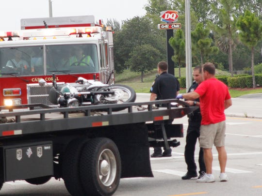 A tow truck takes away the motorcycle of the first fatal shooting victim Sunday evening. Cape Coral police shot and killed a gunman accused of killing the motorcyclist and someone else at a Circle K minutes apart.