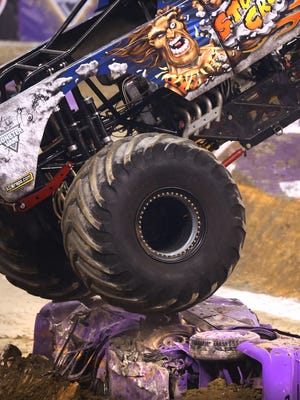 The Stone Crusher truck driven by Steve Sims drives over a car built into a dirt mound during the Monster Jam truck rally held at Lucas Oil Stadium on Saturday night, Jan. 24, 2015.