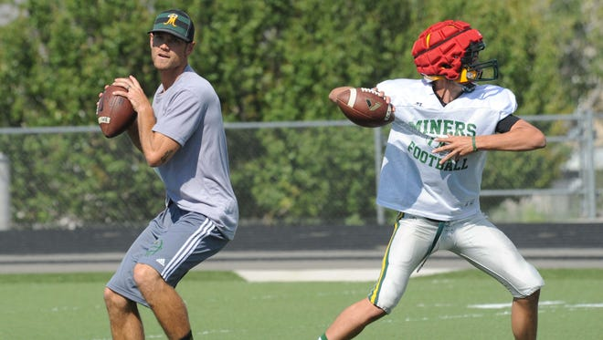 New Bishop Manogue head football coach Thomas Peregrin, a former quarterback at the school, and freshman quarterback Connor Noland at practice on Aug. 20.