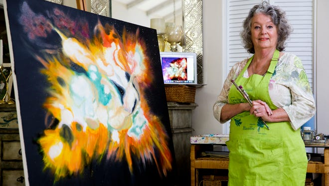 Barbara Sheehan, an abstract painter by trade, stands by her most recent painting depicting the Lynx Arc, a mega cluster of blue-white stars roughly 12,000 million light years away from earth, in her home studio Wednesday, August 3, 2016 in Naples.