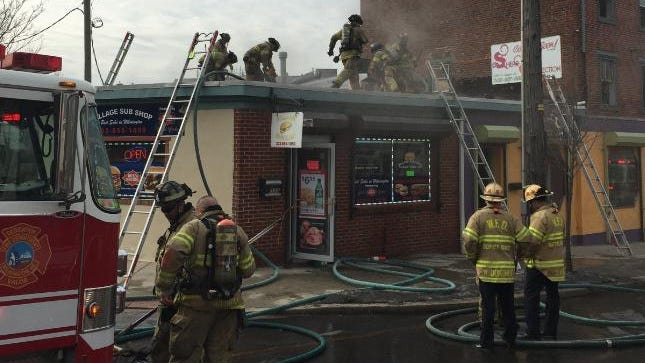 Wilmington firefighters finish putting out a fire Tuesday morning at the Village Sub Shop on Market Street, after which city inspectors condemned the building due to smoke and fire damage.
