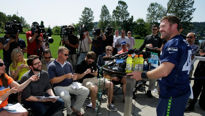 U.S. Army veteran and former Texas long snapper Nate Boyer, right, talks to reporters after Seattle Seahawks NFL football rookie minicamp, Friday, May 8, 2015, in Renton, Wash.